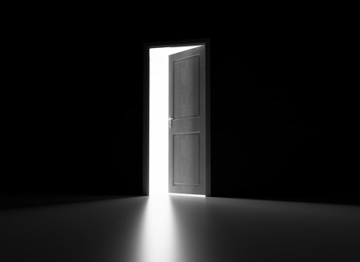 A dark wooden door opens from a blacked-out room to reveal bright white lighting.