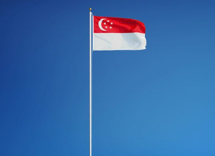 View of a Singapore flag billowing in the breeze on a silver flagpole against a cloudless blue sky on a bright day.