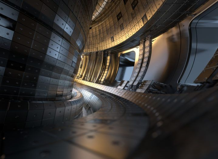 3D illustration of a circular tokamak nuclear fusion reactor chamber, with curved walls and a central core.