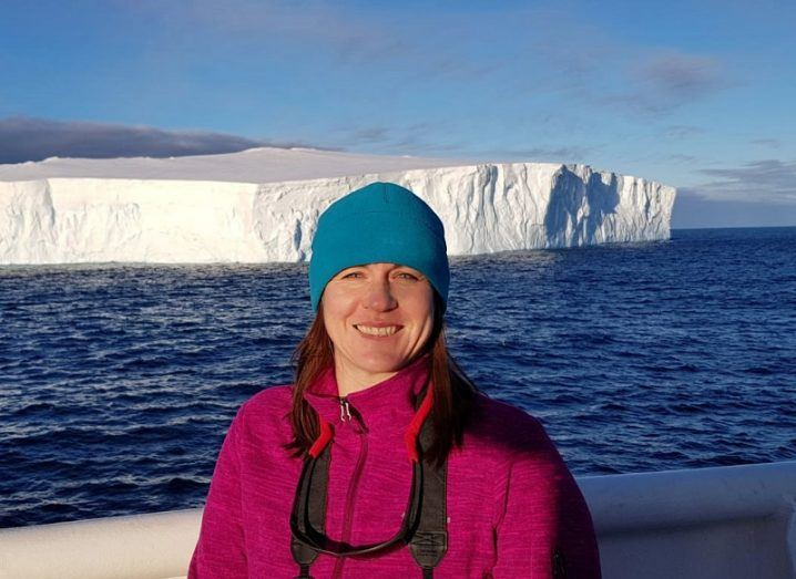 Ailbhe Kavanagh in a pink jacket and blue hat smiling against a backdrop of an Antarctic iceberg.