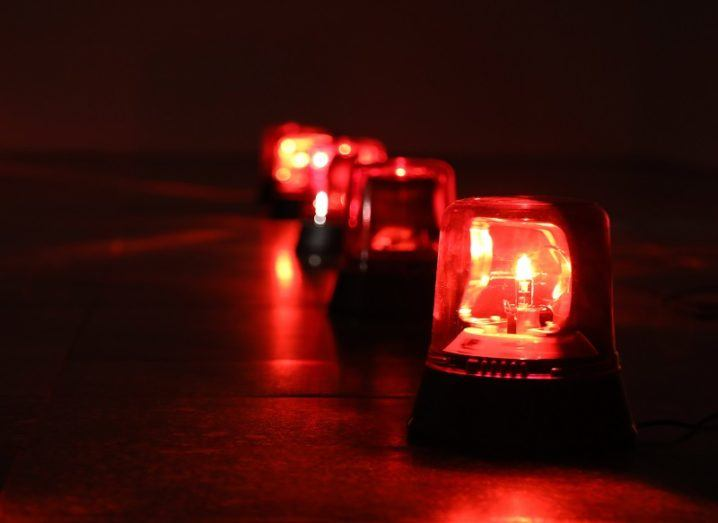 A row of flashing red light alarms in a dark room.