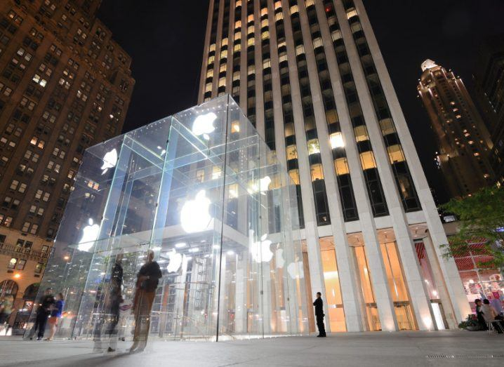 People standing outside an Apple store in New York city at night time.