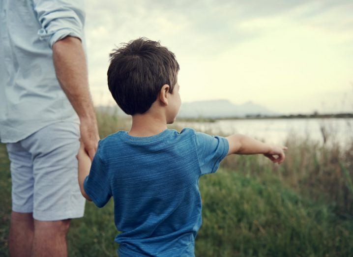 A young boy points at a lake while holding his father's hand.
