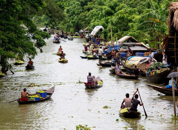 People in small boats on a river surrounded by vegetation and market stalls.