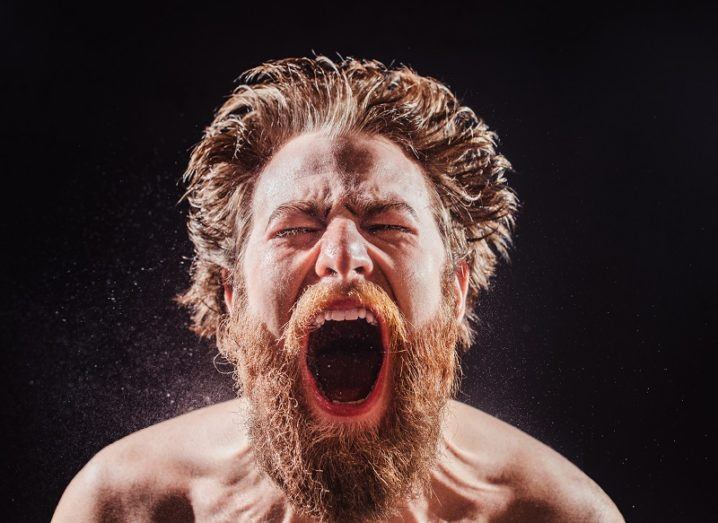 A bearded man without a shirt shouts in a spray of water against a black background.