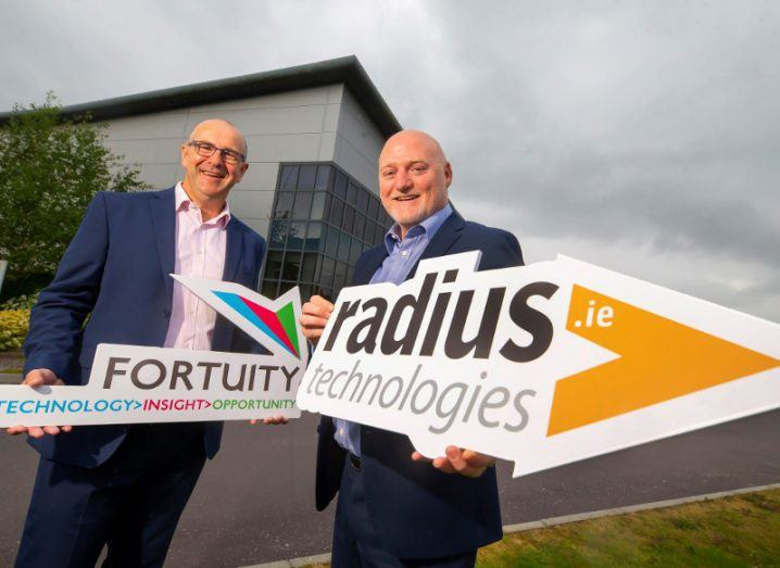 Two men in suits holding signs saying Fortuity and Radius Technologies.