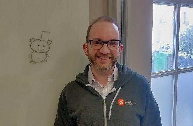 Chris Slowe smiling in a grey Reddit hoodie beside the company's mascot alien, Snoo drawn on a whiteboard.