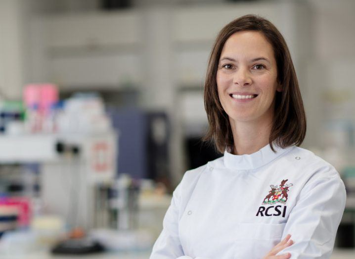A smiling Dr Claire McCoy wears a white RCSI lab coat, standing with her arms crossed by a lab bench.