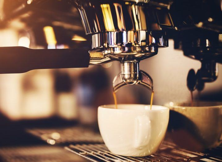 Close-up of a professional coffeemaker pouring coffee into a cup.
