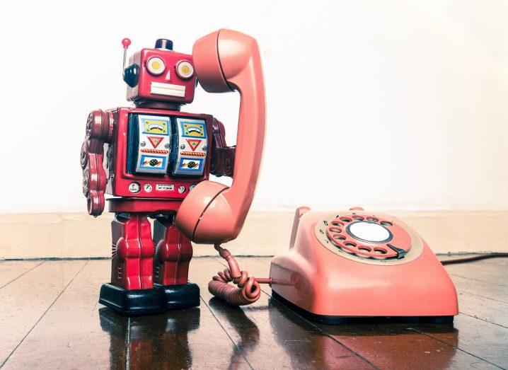 big red robot on the phone standing on a old wooden floor.
