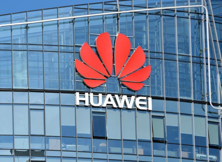 View of red Huawei logo on a glass building with sun shining on it.