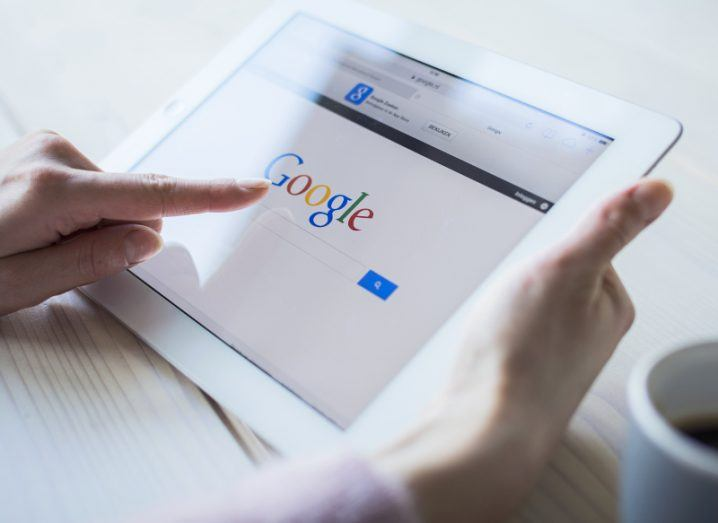 View of a pair of hands holding a white iPad with the Google search homepage displaying on the browser.