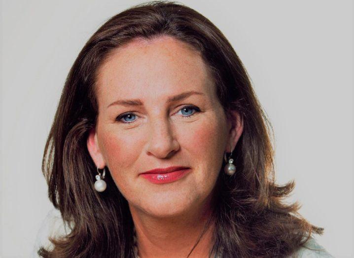 Woman with brown hair and blue eyes wearing pearl earrings.