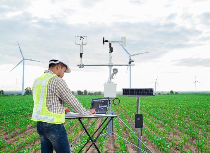 Researcher in high-vis jacket analysing lab equipment in a field with windmills in the background.