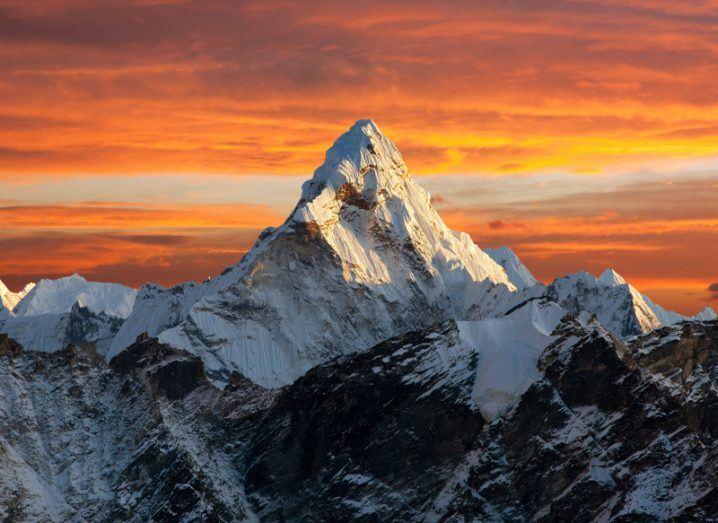 Mount Everest under an orange sky.