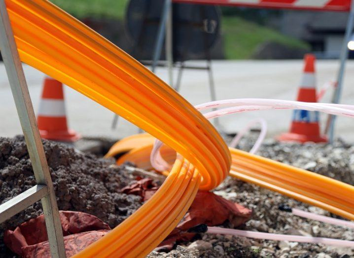 Orange fibre optic cable sticking out of the ground during construction works on a road.