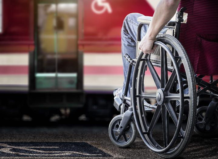 A cropped image of the side of a wheelchair with a man sitting in it at a train station, representing travel accessibility.