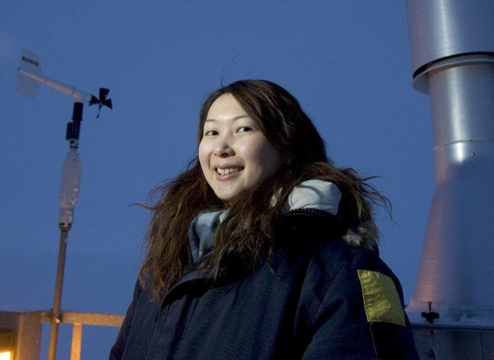 Hayley Hung smiling in a winter jacket surrounded by air monitoring equipment at dusk.