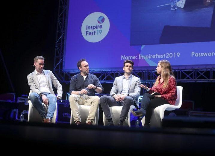 Group of three men one women sitting in white chairs engaged in panel discussion on stage with Inspirefest logo in background.