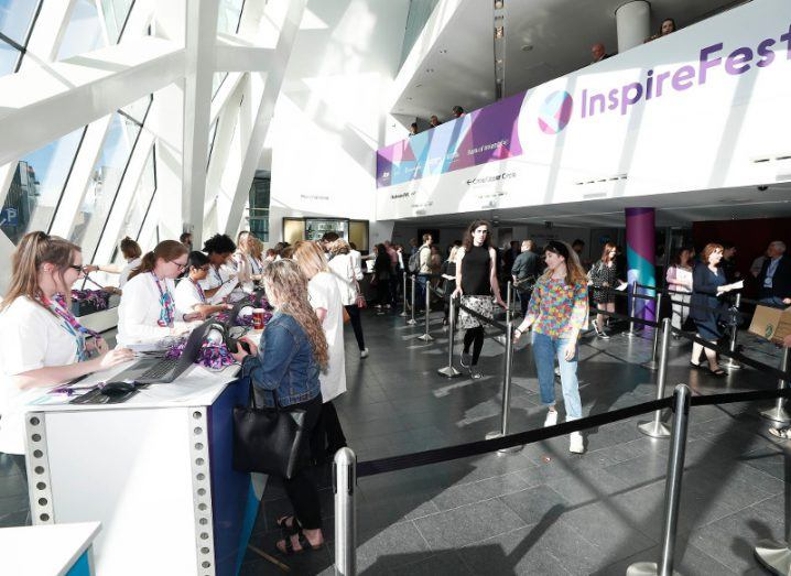 People queuing at Inspirefest 2018 in brightly-lit glass theatre.