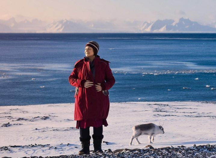 Distant shot of Jenny Hanafin in a long red coat standing against an icy coast off Antarctica.