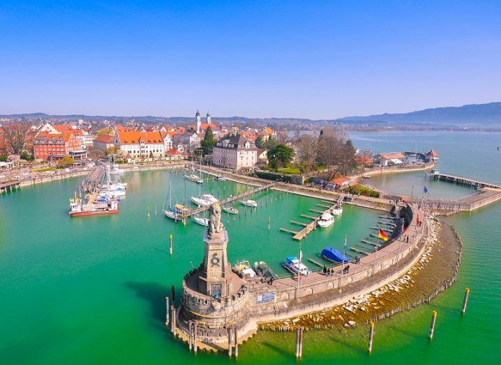 Idyllic seaside town of Lindau with green-blue water, rock wall and harbour against a blue sky.