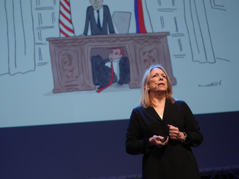 Woman in dark dress standing on stage in front of a political cartoon on screen.
