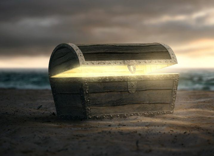 A 3D render of a loot box opening on a beach with glowing gold inside.