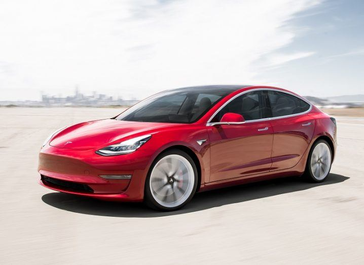 A red Model 3 parked at an angle on tarmac against a city backdrop.