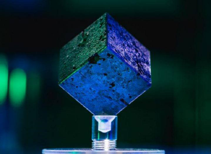 A uranium cube coloured purple, green and blue on a plastic stand.