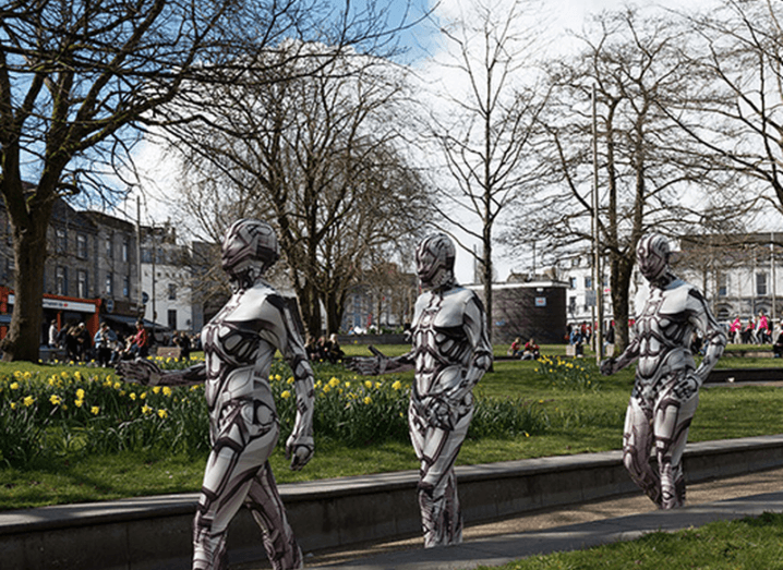 Three people dressed as robots walking mechanically across the NUI Galway campus.