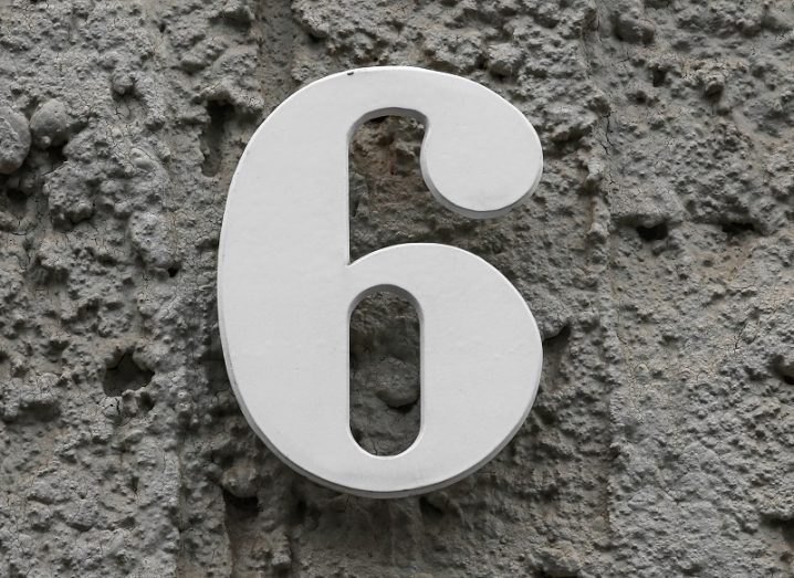 Close-up of a white number six against a grey concrete wall.