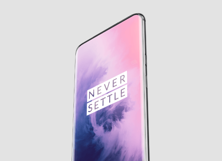 View of a OnePlus 7 smartphone with the words never settle on the screen.