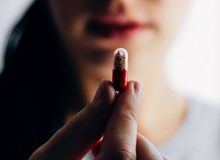 Blurred woman holding up a red and white painkiller pill in centre focus.