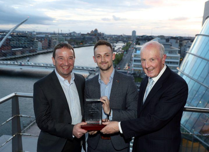 Three men hold an award on a balcony on a building overlooking the River Liffey.