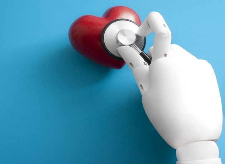 A white robotic hand holding a stethoscope to a red heart against a blue background.