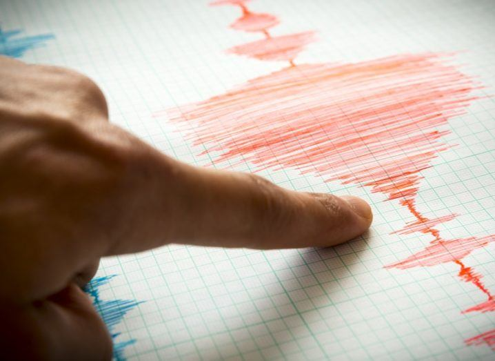 Close-up of a finger pointing to seismic data on a sheet following an earthquake.