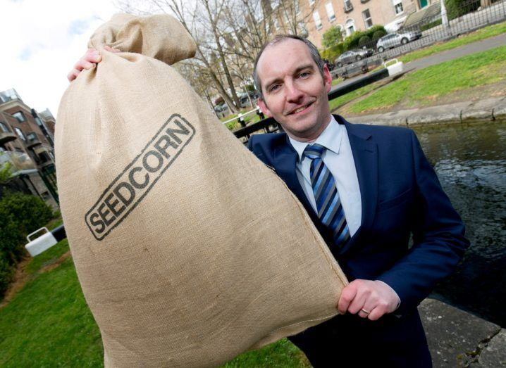 Man holds a Seedcorn bag in front of a canal.