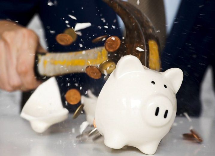 Close-up of a person in a blue suit smashing a white piggybank with a hammer on a grey countertop.