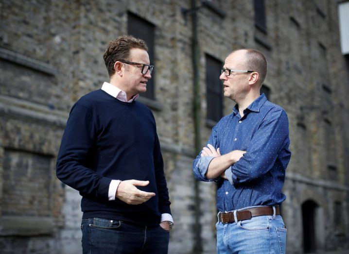 Two men in glasses and wearing jeans talking on a Dublin street.