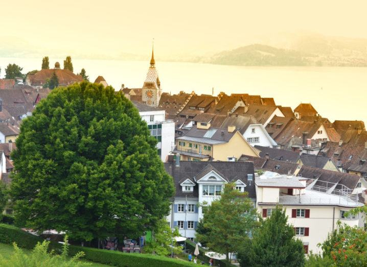 A view of the canton town of Zug beside a misty lake.