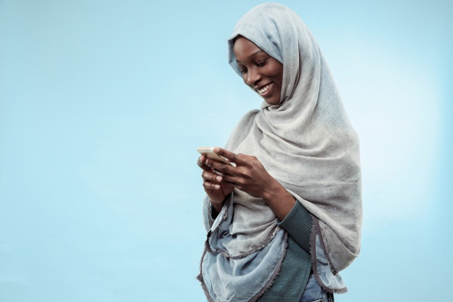 African woman in a hijab smiling at her smartphone.