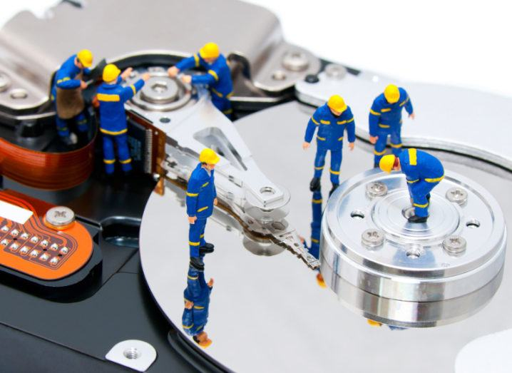 close-up of miniature toy men wearing blue overalls and yellow hard hats, examining a silver hard disk, trying to recover lost data.