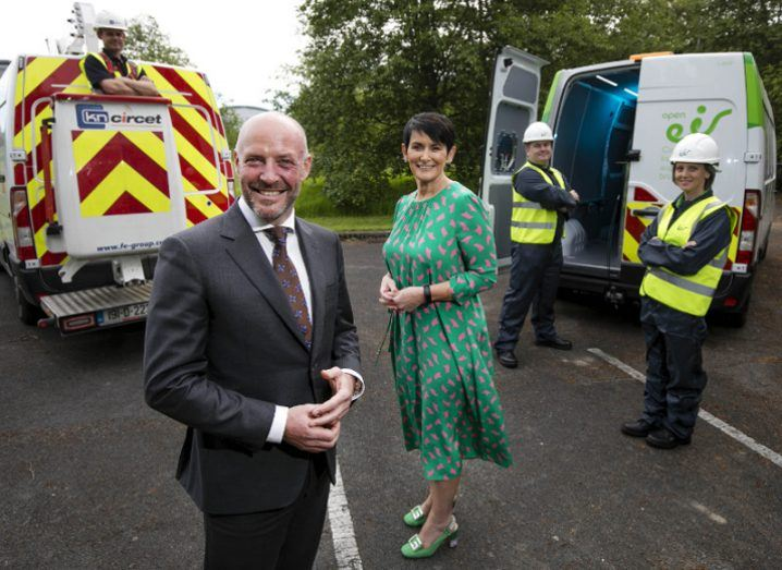 Man in suit and woman in green dress stand next to telecoms equipment vans.