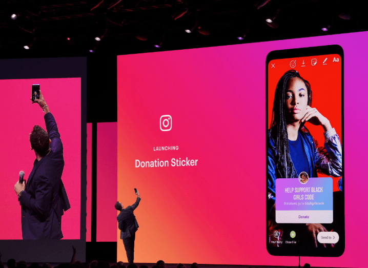 A man takes a picture on stage indicating how a new donation sticker works on Instagram.