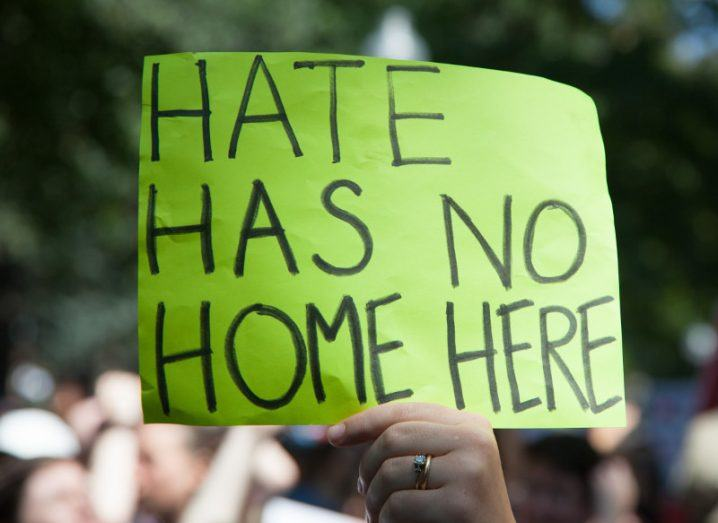 A protester against hate speech holds up a neon green sign that says 'hate has no home here'.