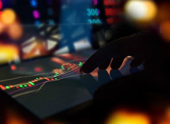picture of a hand touching a digital screen with coloured graphs indicating share prices.