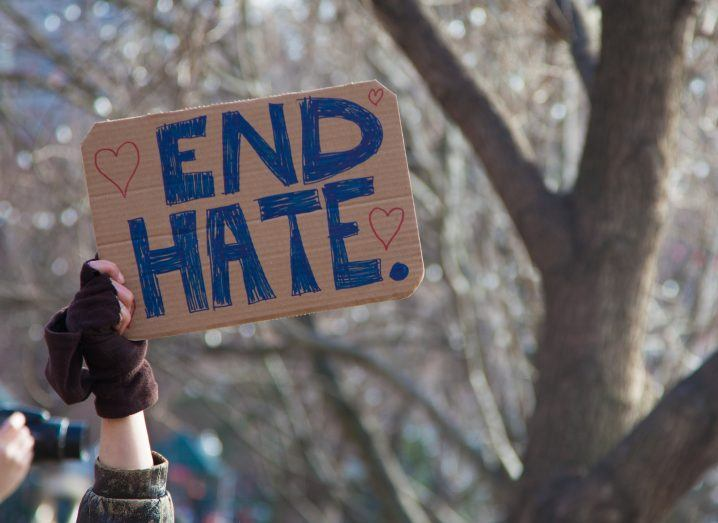 "Hand holding sign saying ""End Hate""."