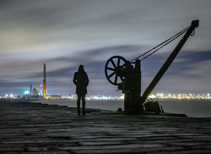 Woman stands looking at lights of Dublin beside a crane at Poolbeg light tower.