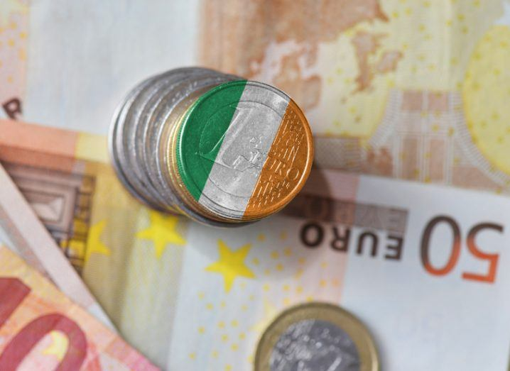 euro coin painted with colours of irish flag sitting on 50 euro note.